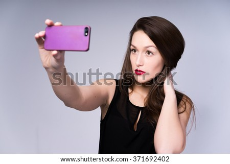 Sexy brunette girl with long hair, red lips makeup in the black dress taking selfie. Studio portrait isolated on grey background.