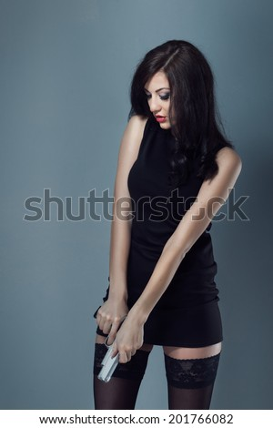 sexy brunette girl with makeup and red lips in black dress and stockings boots holding a gun and reload it - stock photo
