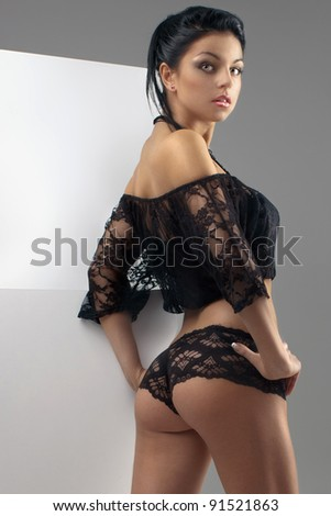sexy brunette in a provocative black lingerie posing in the studio - stock photo