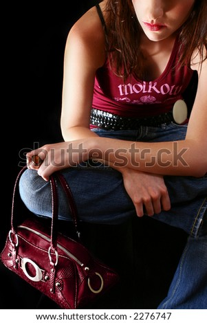 Sexy brunette in a t-shirt and jeans, sitting and holding a red handbag.  Looking down. - stock photo