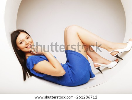 sexy brunette in blue dress sitting in a circle - stock photo