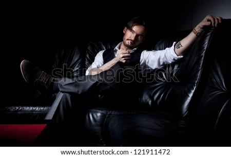 Sexy brunette man lies on the black couch - stock photo