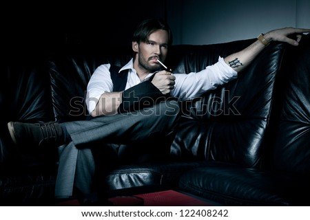 Sexy brunette man on the black couch smoking a cigarette - stock photo