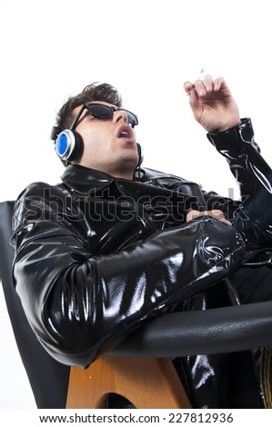 Sexy brunette man on the black couch smoking a cigarette , isolated on white background  - stock photo