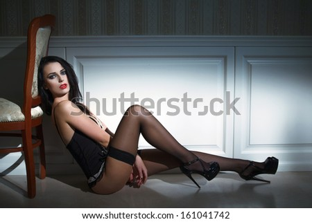 Sexy brunette model sitting on the floor at night - stock photo