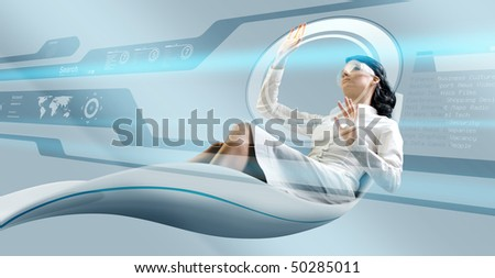 Sexy brunette operating interface in futuristic armchair - Attractive young adults in futuristic interfaces / interiors series - stock photo