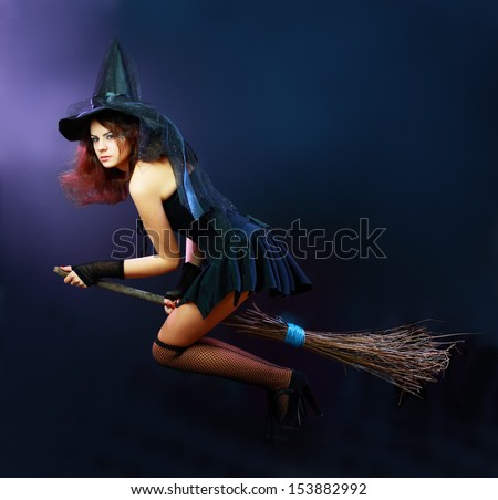 Sexy brunette witch flying on broom on a dark  - stock photo