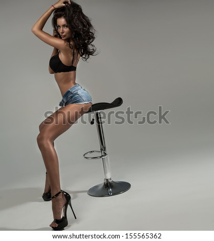 Sexy brunette with long legs posing. Photo with space for your text - stock photo