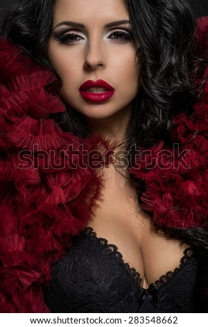 Sexy brunette woman in black underclothes and red fluffy bolero on dark background - stock photo