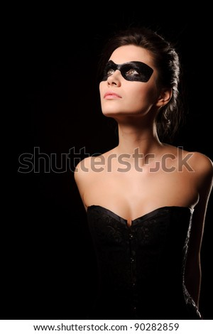 Sexy brunette woman in corset and black mask on the face, isolated on black - stock photo