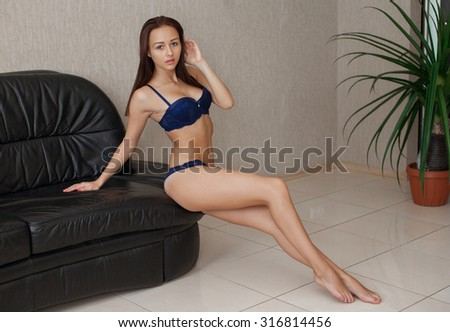 sexy brunette woman in seductive black lingerie sitting on a couch in stockings - stock photo
