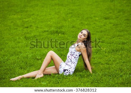 Sexy brunette woman in short dress sitting on green grass