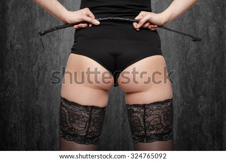 Sexy brunette woman in stockings holding whip, back view, at gray wall - stock photo
