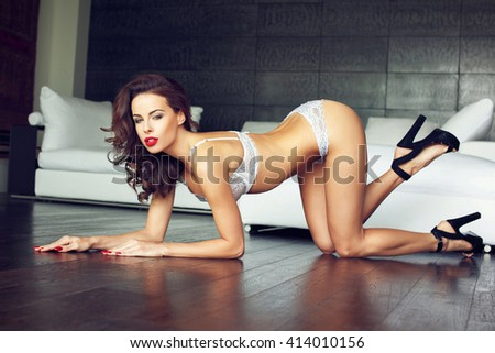 Sexy brunette woman in white underwear kneeling on floor, red lips, glamour - stock photo
