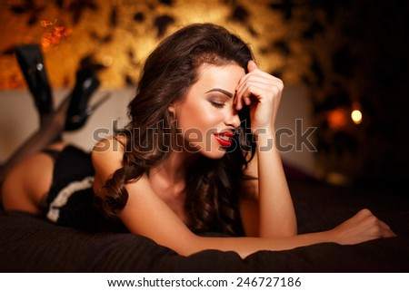 Sexy brunette woman laying on bed at night, closed eyes, sensuality - stock photo