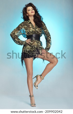Sexy brunette woman posing in fashionable clothes over blue studio background - stock photo