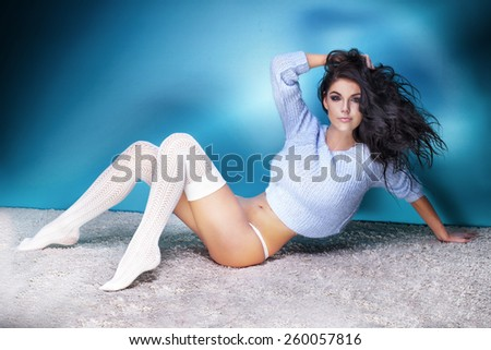 Sexy brunette woman posing in studio, lying. Girl with long curly hair. - stock photo
