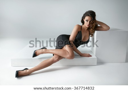Sexy brunette woman posing isolated in fashionable black dress - stock photo