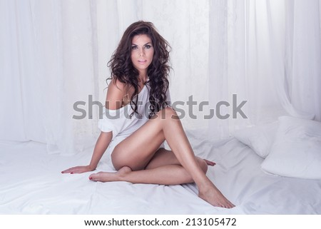 Sexy brunette woman sitting in big white bed, relaxing. Girl looking at camera - stock photo
