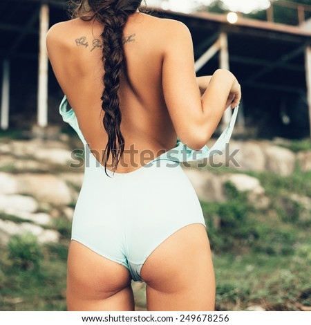 sexy brunette woman taking off her bikini against a sky. outdoor lifestyle portrait - stock photo