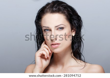 Sexy brunette woman with wet hair beauty on grey - stock photo