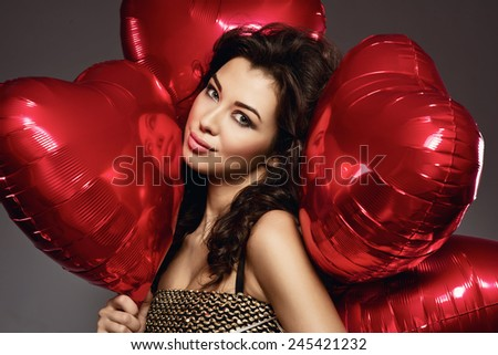 sexy brunette young woman in golden dress with a heart-shaped balloons. Valentine's day - stock photo