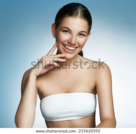 Sexy brunette young woman posing / portrait of a young beautiful brunette woman toothy smile on blue background  - stock photo