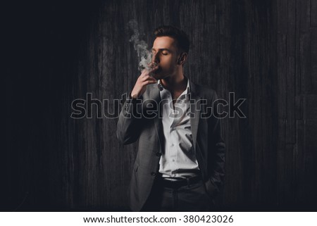 Sexy brutal man in gray suit smoking a cigar - stock photo
