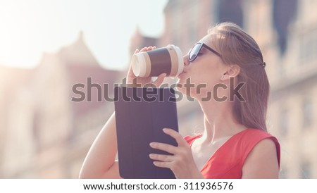 Sexy Business Woman using digital tablet. Slow Motion. Beautiful woman red dress enjoying sunny morning in the city, browsing Internet and drinking coffee. Lens Flare. - stock photo