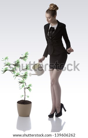 sexy business woman with blonde hair and elegant black suit watering green 100 euro money plant with watering can