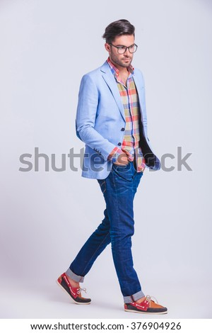 sexy casual guy walking in studio background with hands in pockets while posing looking away from the camera - stock photo