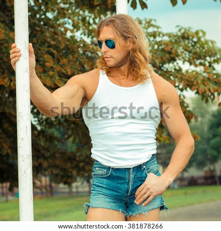 sexy caucasian fit man in sunglasses posing near Sports Bars Outdoors. Strong and confident man posing outdoor - stock photo