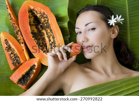 Sexy caucasian woman eating Fresh Papaya slices. Healthy exotic vitamin food (outdoors, tropical palm leafs background) - stock photo