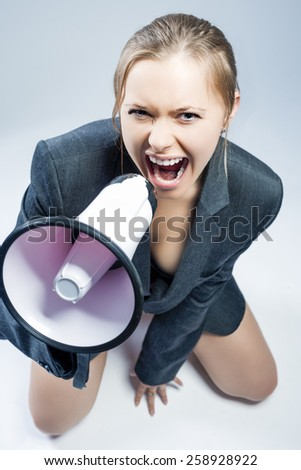 Sexy Caucasian Woman in Lingerie and Suite Screaming Using Megaphone. Sitting Against Gray Background. Vertical shot - stock photo