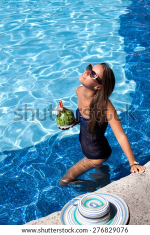 Sexy cheerful woman in bikini relaxing at the luxury poolside. Girl at travel spa resort pool. Summer luxury vacation.  - stock photo