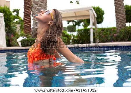 Sexy cheerful woman relaxing at the luxury poolside. Girl at travel spa resort pool. Summer luxury vacation. - stock photo