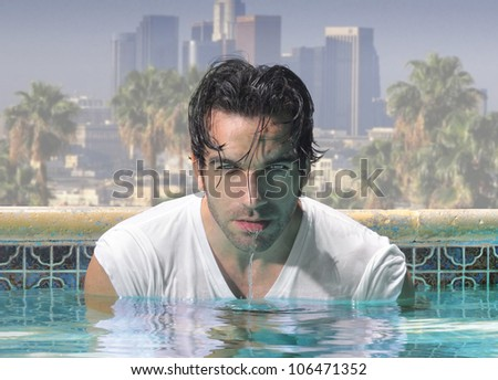 Sexy close-up portrait of a handsome man in glamorous swimming pool with city background - stock photo