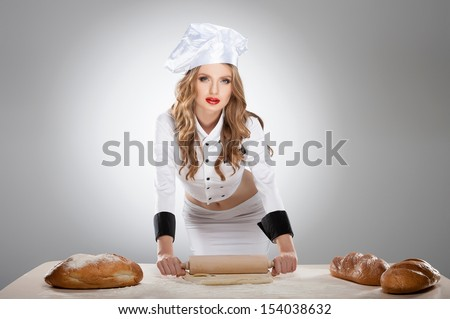 Sexy cook. Beautiful young woman in Chef costume standing isolated on grey - stock photo