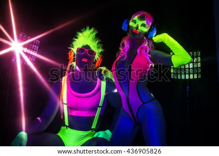 sexy couple disco party dancers posing in UV costume - stock photo