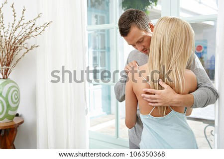 Sexy couple hugging and kissing at home.
