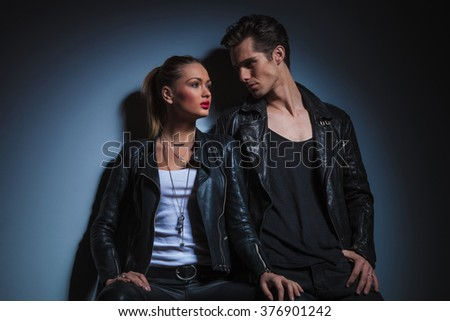 sexy couple in leather pose in dark studio background, man lean on the wall looking at the woman and she pose looking away - stock photo