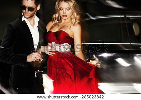 Sexy couple in the car. Hollywood star. Fashionable pair of elegant people at night city street. - stock photo