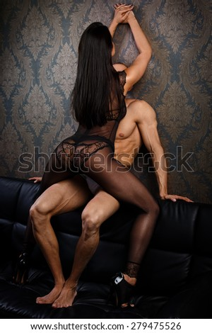 Sexy couple in underwear on leather sofa - stock photo