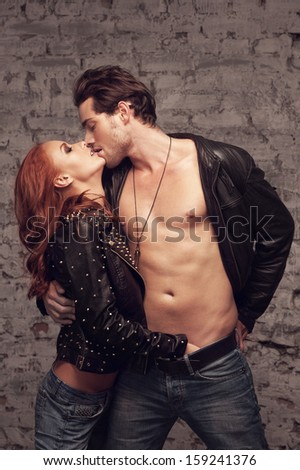 Sexy couple kissing. While girl putting her hand in man jeans - stock photo