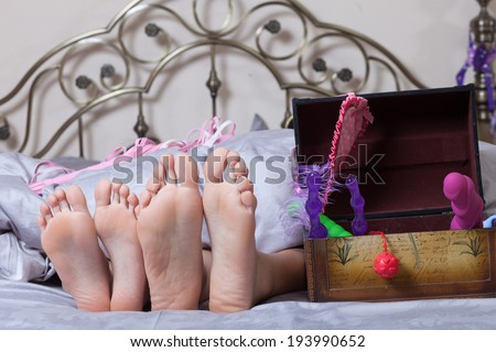 sexy couple lying in bed. use sex toys. - stock photo