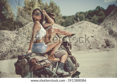 Sexy couple of bikers on the old motorcycle. Artistic toning.