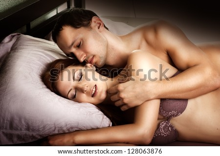Sexy couple of  lovers. Young man kissing woman in darkness bedroom on bed