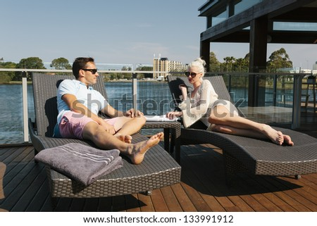 Sexy couple relaxing on sunbeds - stock photo