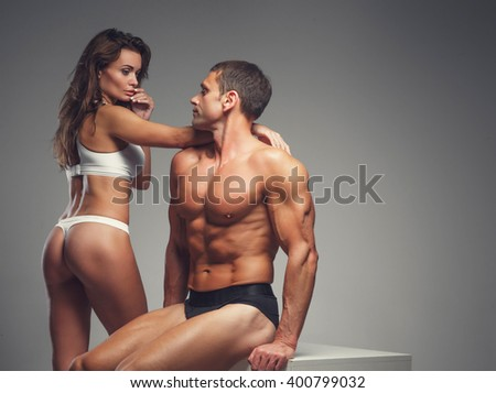Sexy couple. Shirtless muscular middle age man and a woman in underwear posing in studio.