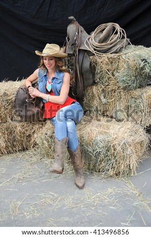 Sexy cowgirl relaxing inside a barn on haystacks.